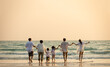canvas print picture - Happy multi generation Asian family holding hands and walking on the beach together at summer sunset. Smiling big family parents with child boy and girl enjoy in outdoors lifestyle travel vacation