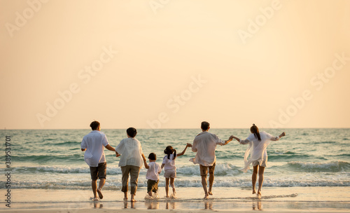 Happy multi generation Asian family holding hands and walking on the beach together at summer sunset. Smiling big family parents with child boy and girl enjoy in outdoors lifestyle travel vacation