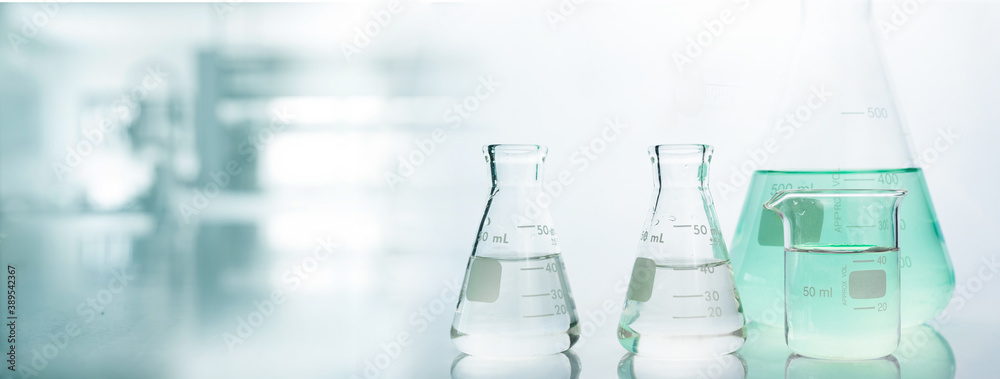 Fototapeta flask and beaker in chemistry science laboratory banner background