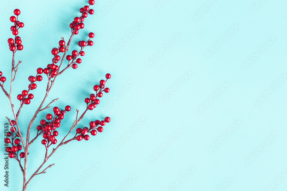 Fototapeta Christmas composition. Red berries on blue background. Christmas, winter, new year concept. Flat lay, top view