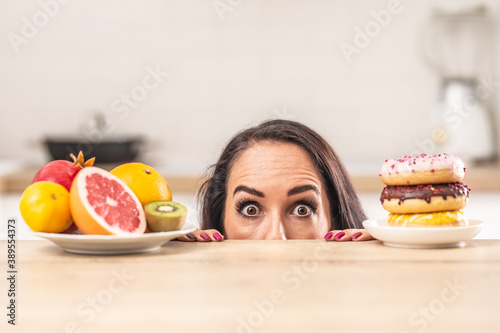 A matter of choice for a woman peeking above the table where plate full of fruit Wallpaper Mural