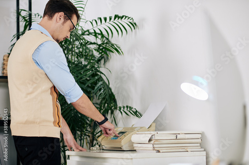 Young businessman in shirt and waistcoat receiving fax when working in office Fototapeta