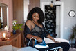attractive overweight african woman use modern flatiron for ironing clothes, morning, female stands in underwear in living room