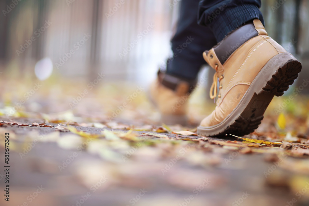 Fototapeta Autumn concept. Pedestrian feet on the road. Autumn leaves on the footpath.