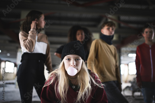 Fototapeta Teenager girl with friends standing indoors in abandoned building, making bubble gum. obraz