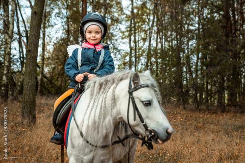 Little girl on a white pony on a background of nature. Jockey, hippodrome, horseback riding.