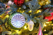 Toy Flower And Pine Cone Branch As Decoration For New Years Celebration. Winter Christmas Tree With Bauble