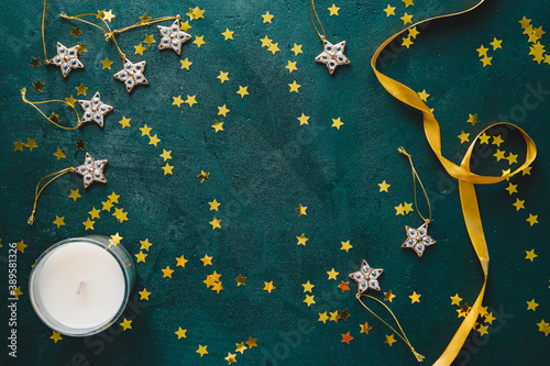 Obraz The New Year or Christmas festive flat lay with golden stars over a dark green background. Top view, copy space. - fototapety do salonu