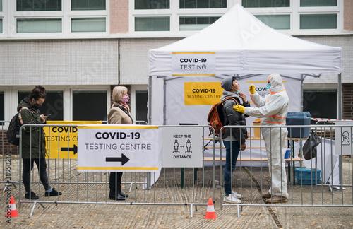 Fototapeta People waiting in covid-19 testing center outdoors on street, coronavirus concept