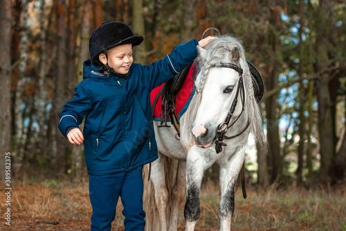 Boy in a jockey cap portrait, stands next to a white pony close-up on the background of nature. Jockey, epodrome, horseback riding.