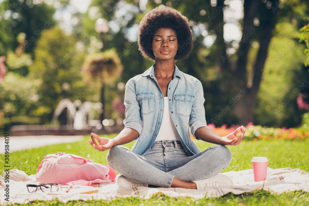 Fototapeta Photo portrait of black skinned young woman sitting in city green park near bag doing yoga asana lotus having pause chill rest closed eyes
