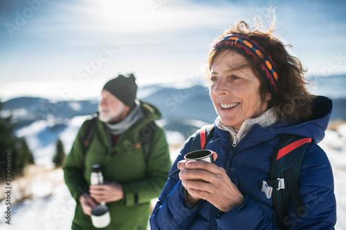 Fototapeta Senior couple hikers in snow-covered winter nature, drinking hot tea. obraz