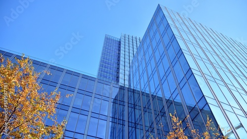 Blue curtain wall made of toned glass and steel constructions under blue sky. A fragment of a building.