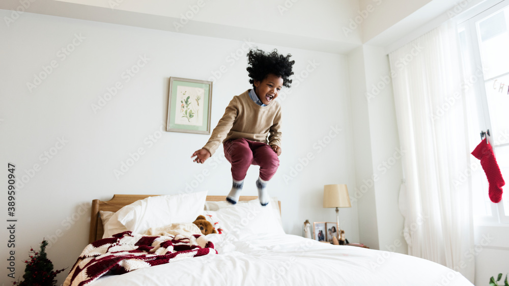 Fototapeta Young kid having a fun time jumping on the bed