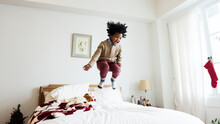 Young Kid Having A Fun Time Jumping On The Bed