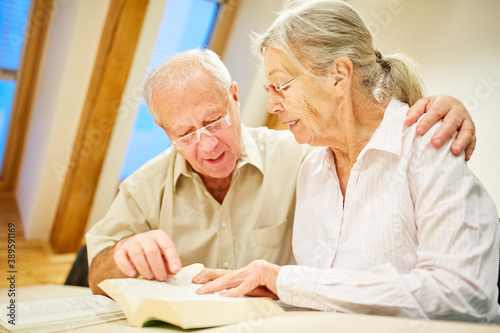 Senior couple with book reading and reading aloud Wallpaper Mural