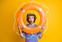 Photo Of Amazed Guy In Scuba Goggles Gear Hold Life Buoy Near Face Wear Frock Isolated Over Yellow Color Background