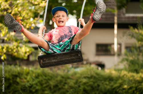 Photo Boy has great fun swinging in the park