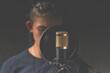 Leinwandbild Motiv Studio microphone for sound recording. The singer in the background blurred background. Low key lighting