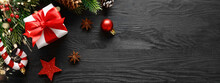Gift Box With Christmas Decorations On Black Wooden Background