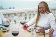 canvas print picture - African senior woman having dinner and drinking wine with friends at home dinner - Focus on face