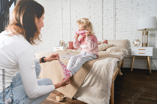 Leinwand Poster Mom takes off her little daughter's socks and tickles her feet a little