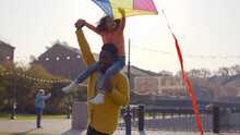 Cute African Little Girl Sitting On Shoulders Of Dad And Playing With Colorful Kite
