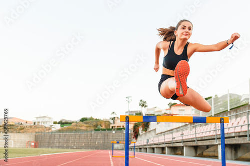 Fotografering Fit female teenager athlete hurdler running jumping over hurdles - Copy space