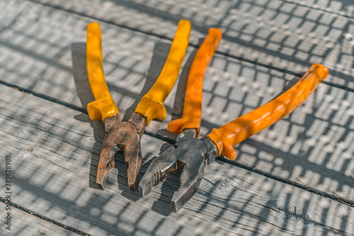 A pair of old and rusty father's pliers lie on a wooden table in the workshop Canvas Print
