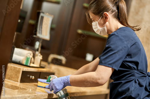 Housemaid in uniform and protective gloves cleaning the hotel bathroom Fototapet