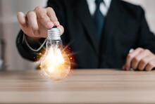 Business Man Holding A Light B...