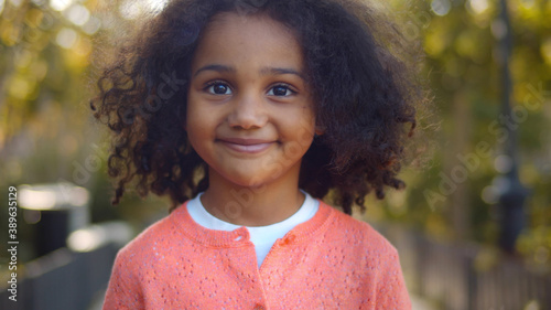 Obraz Close up of happy cute little african girl smiling at camera outdoors - fototapety do salonu