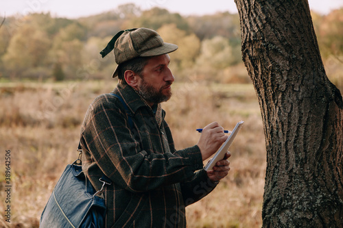 Scientist examines a tree trunk in autumn park Fototapet