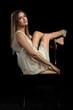 piękna seksowna modelka kobieta dziewczyna w studiu w białej sukience na czarnym tle na krześle