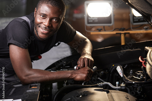 repairing in action. hardworking guy employee in uniform works in the automobile salon, confident auto mechanic is professional worker of service