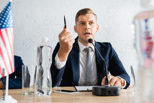Serious politician gesturing with pen, while speaking in microphone and sitting Fototapeta