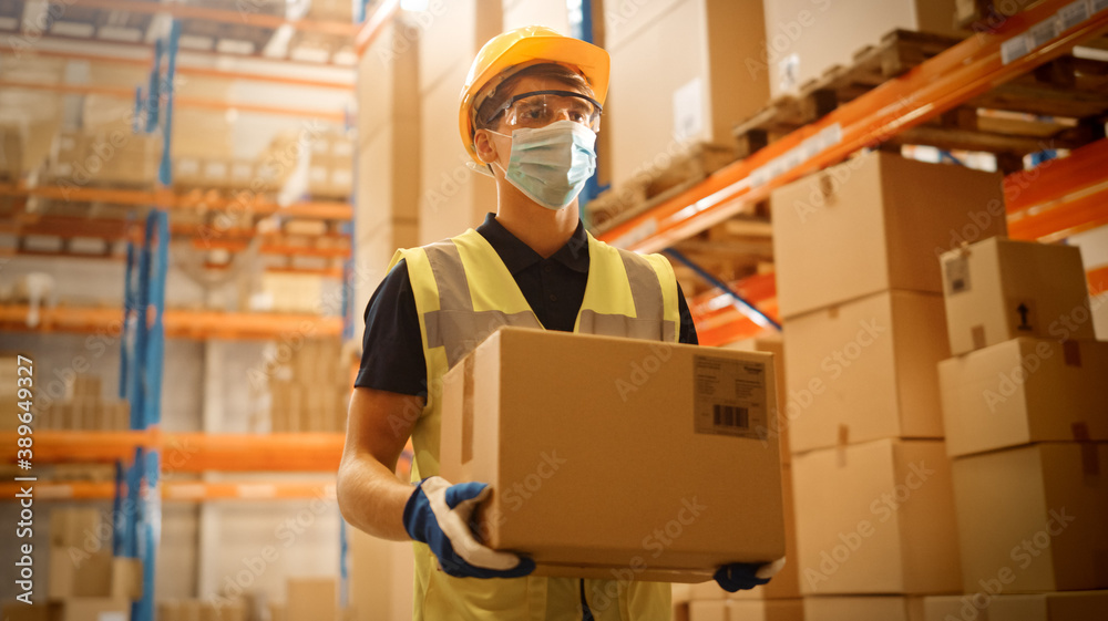 Fototapeta Portrait of Handsome Male Worker Wearing Medical Face Mask and Hard Hat Carries Cardboard Box Walks Through Retail Warehouse full of Shelves with Goods. Safety First Protective Workplace.