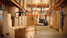 Big Retail Warehouse Full Of Shelves With Goods Stored On Manual Pallet Truck In Cardboard Boxes And Packages. Forklift Driving In Background. Logistics And Distribution Facility For Product Delivery