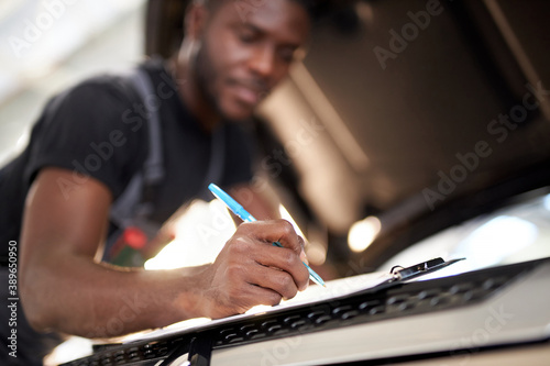 Carta da parati african auto mechanic making notes during work, focus on pen and notebook