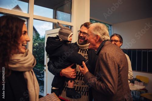 Fototapeta Family coming over to grandparents for Christmas eve celebrations