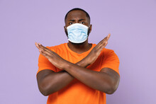 Displeased Young African American Man In Orange T-shirt Sterile Face Mask To Safe From Coronavirus Virus Covid-19 Showing Stop Gesture With Crossed Hands Isolated On Violet Background Studio Portrait.