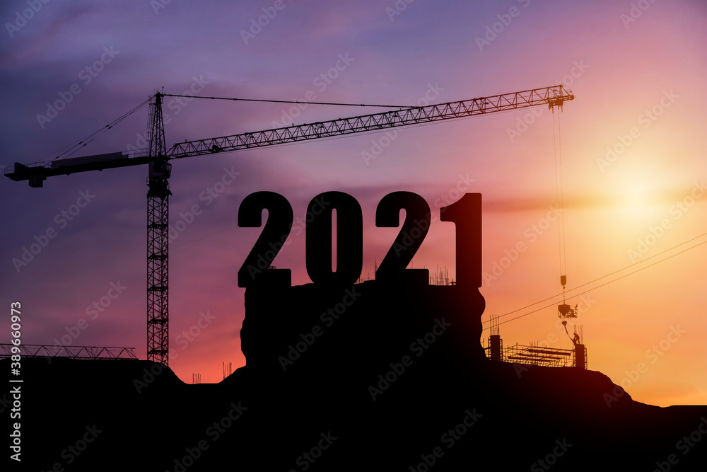Fototapeta Cranes building construction 2021year sign. Silhouette staff works as a team to prepare to welcome the new year 2021