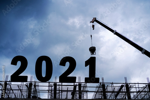 Leinwand Poster Cranes building construction 2021year sign,Silhouette staff works as a team to p