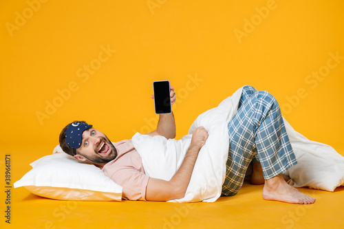 Full length of surprised man in pajamas home wear sleep mask lying hold mobile phone with blank empty screen isolated on yellow colour background studio portrait Fotobehang