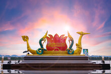 This Is Lan Phanom Naka. It Is Landmarks Along Mekong River, Nakhon Phanom, Thailand. Two King Naga Big Snake And The Beautiful Golden Boat On The Colorful Sky Background.