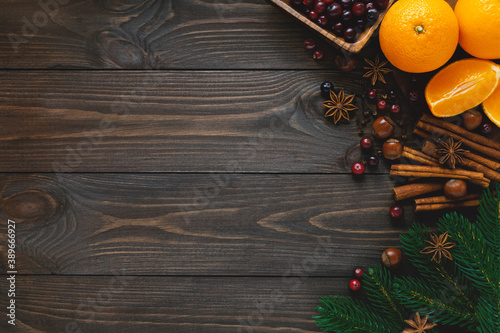 Christmas spices and ingredients for holiday cooking and drinks on dark wooden background. Flat lay, top view, copy space.