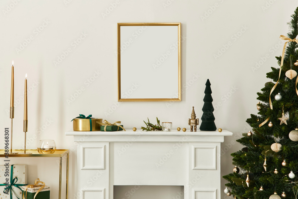 Fototapeta Christmas composition with gold mock up poster frame, white chimney and decoration. Christmas trees and wreath, candles, stars, light and elegant accessories. Template.