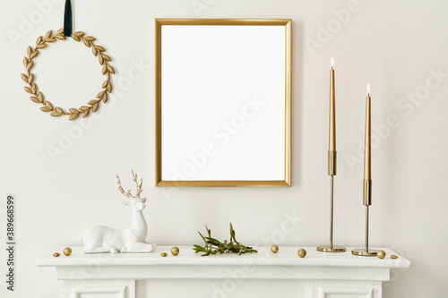 Fototapeta Christmas composition with gold mock up poster frame, white chimney and decoration. Christmas trees and wreath, candles, stars, light and elegant accessories. Template. obraz