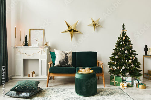 Stylish christmas living room interior with green sofa, white chimney, christmas tree and wreath, stars, gifts and decoration Fototapet