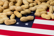 Closeup Of Peanuts In Shell On Flag Of United States Of America. Concept Of Peanut Farming, Trade, Tariffs And Market Price